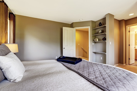 Bedroom interior with carpet floor and big bed. American northwest house