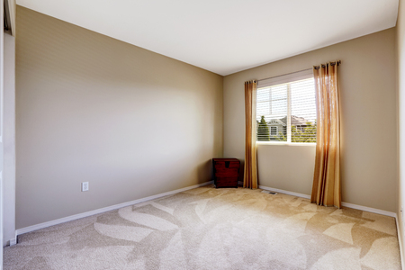 contemporary house: Bright empty room with one window, beige carpet floor and ivory walls Stock Photo