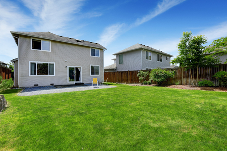 lawn area: Spacious backyard area with dark brown wooden fence and green lawn