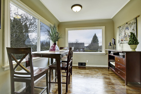 designer chair: Large green dining room with wooden chairs and large windows.