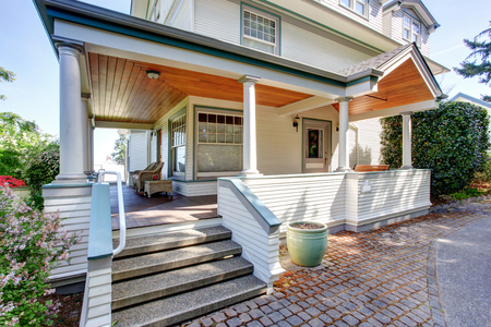 home exterior: Front porch with chairs and columns of craftsman style home. Stock Photo