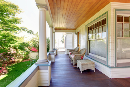 Front porch with chairs and columns of craftsman style home.