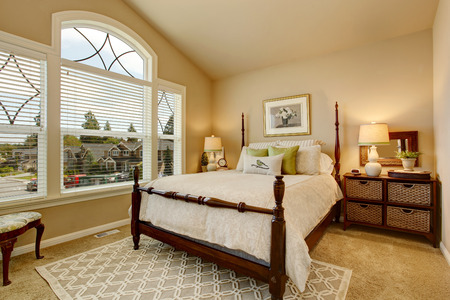 Cozy Beige bedroom with vaulted ceiling, large window and elegant Victorian style bed.