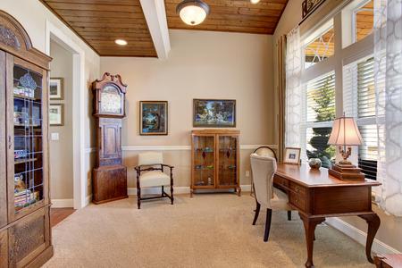 oficina en casa con muebles de época, suelo de moqueta y paredes de color beige
