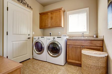 machine à laver: Salle de lavage avec laveuse et sécheuse. Armoires en bois et carrelage