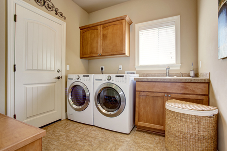 Wasruimte met wasmachine en droger. Houten kasten en tegelvloer