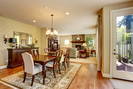 classic living room: Classic American dining room with wooden table set, hardwood floor and rug. Also connected to living room Stock Photo