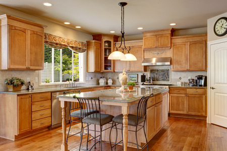 counter top: Classic American kitchen inerior with brown cabinets, granite counter top, island and hardwood floor