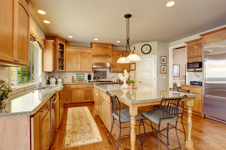 kitchen counter top: Classic American kitchen inerior with brown cabinets, granite counter top, island and hardwood floor