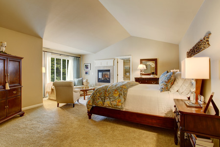 bedroom furniture: Classic american bedroom with wooden furniture, carpet floor and fireplace