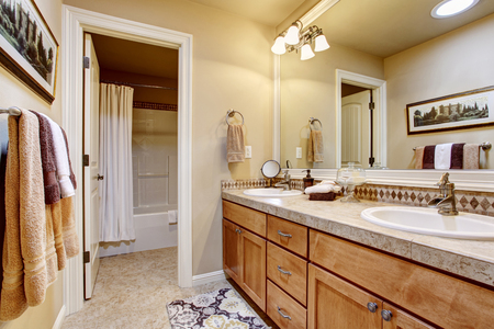 white trim: Elegant bathroom interior with large mirror, granite counter top and tile floor. Beige walls with white trim.