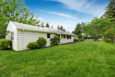 rambler: Fenced Back yard of American rambler with green grass and lots of space. Stock Photo