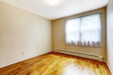 house windows: Small empty basement room with hardwood floor, white ceiling and beige walls Stock Photo