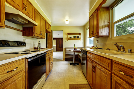 cabinets: Light narrow kitchen room with corner sofa, small table, wooden cabinets and tile floor