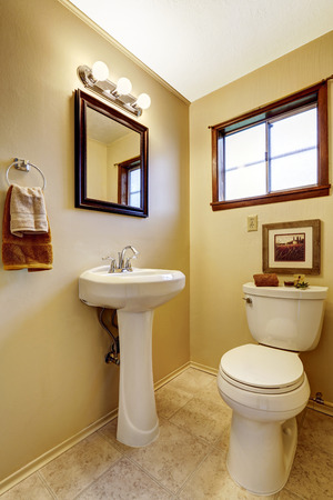 old frame: Bright beige bathroom interior with old washbasin stand, toilet and tile floor. Also mirror in wooden frame with lights.