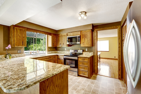 wood stove: Kitchen interior with wooden cabinets, tile floor and granite counter top