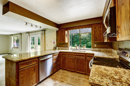 counter top: Kitchen interior with wooden cabinets, tile floor and granite counter top