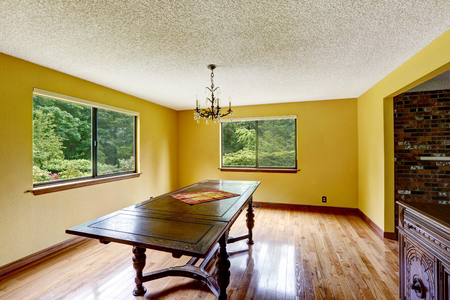 yellow walls: Empty dining room with antique furniture, hardwood floor and painted yellow walls