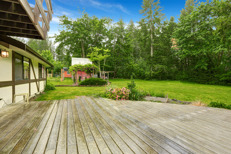 lawn area: View of wooden walkout deck with patio area. Backyard garden with green lawn.