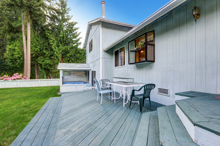 deck: Blue walkout deck with patio table and chairs. View of hot tub. House exterior.