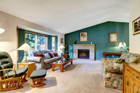 classic living room: Elegant white and green living room. Classic American design: brick fireplace, carpet floor, rocking chair and colorful sofa