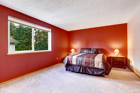 nightstands: Red bedroom with beige carpet floor and bright colorful bedding. Two nightstands with lamps and one window.