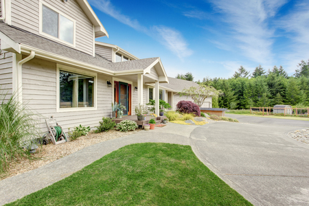 white trim: Large beige house with white trim, and well kept lawn, along with three garage spaces and driveway