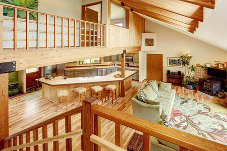 View from the wooden staircase into the living room and kitchen room. Wooden beams on the ceiling. 免版税图像