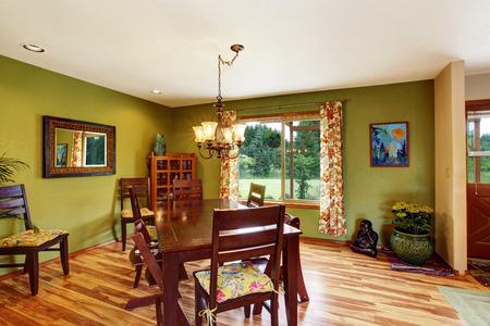 caoba: interior verde antiguo comedor con juego de mesa de caoba y l�mpara de ara�a. piso de madera y techo blanco.
