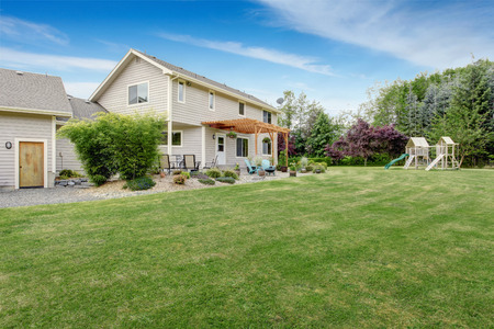 country house style: Beautiful house backyard with well kept lawn, patio area and playground at the background
