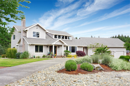 white trim: Large beige house with white trim, and well kept lawn, along with three garage spaces and landscaping desing