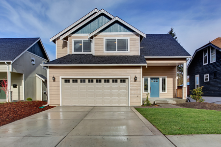 white window: House exterior. American beige house with green grass. Garage with driveway
