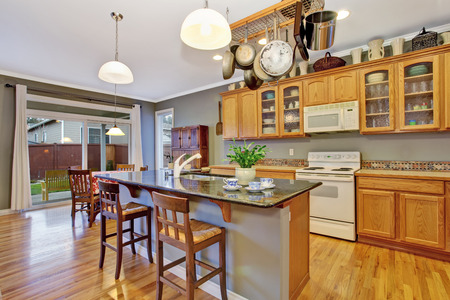 kitchen cabinets: Kitchen with bright wooden cabinets, steel appliances and granite tops. Kitchen room has kitchen island