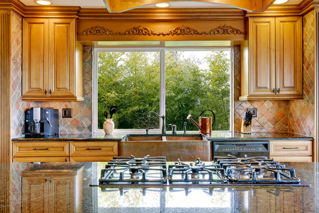 kitchen cabinets: Narrow beige and yellow kitchen with cabinets and big window
