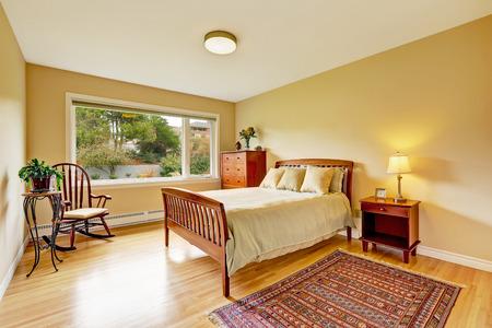 bedroom furniture: Bedroom with hardwood floor, bright walls and wooden furniture set Stock Photo