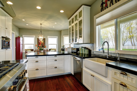 cocina vieja: Cocina vacía vieja simple, con piso de madera y muebles blancos, encimera negro en la casa histórica de América. Conectado al comedor