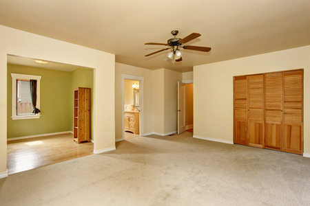 Old craftsman style house with beige interior paint. Carpet floor and built-in closet in empty room.