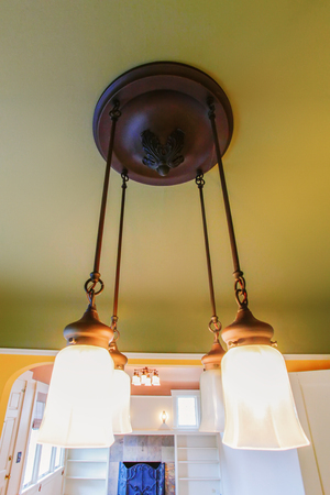 remodeled: Classic ceiling chandelier close up. Empty room interior with green ceiling