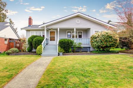 Beige het opruimen huis buitenkant met overdekte veranda en bijgesneden struiken aan de voorkant. Uitzicht op zachte blauwe trap met smalle loopbrug.
