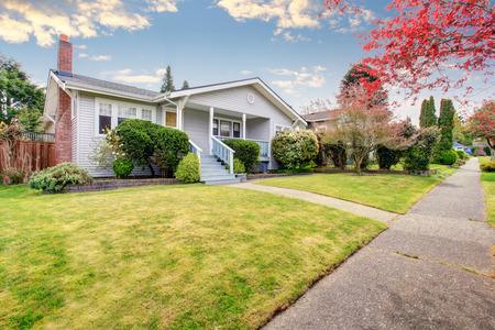 베이지 색 사이딩 집 외관 덮여 현관과 파란색 계단. 트림 된 관목과 앞뜰에 녹색 잔디의 전망.