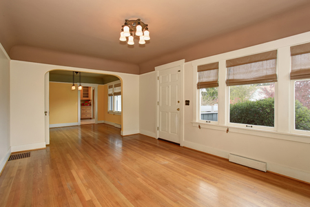 Empty living room interior with mocha ceiling, hardwood floor and white walls. View of arched doorway leading to other rooms. Stock Photo