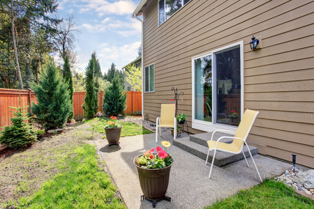 garden styles: Nice backyard with concrete patio area . House exterior. Stock Photo