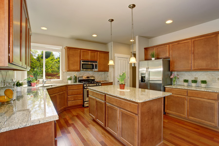 kitchen island: Kitchen room interior with hardwood floor, brown cabinets and granite counter top. Also there is island