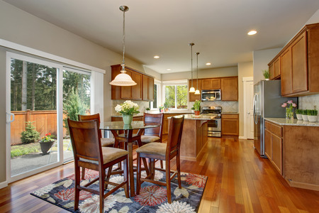 kitchen counter top: Kitchen room interior with hardwood floor, brown cabinets and granite counter top. Connected to dining area Stock Photo