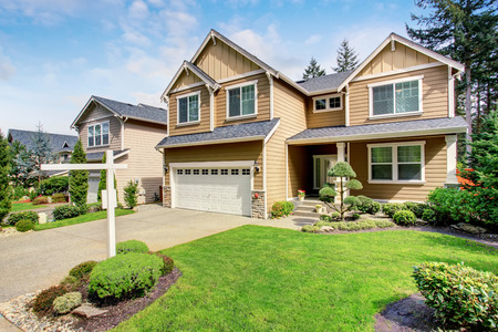 curb appeal: Nice curb appeal of American two story house with perfect landscape design. Beige exterior paint with white trim