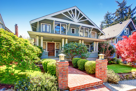 Large luxury blue craftsman classic American house exterior. View of brick walkway decorated with trimmed hedges. Foto de archivo