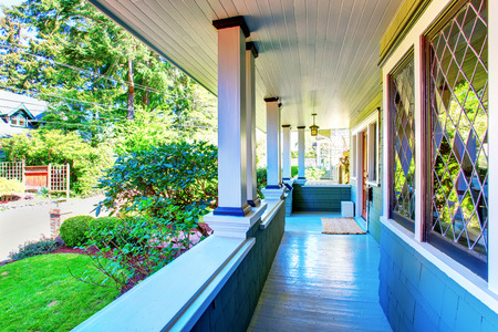 Perfect covered front porch in blue colors with decorative windows, and greenery.