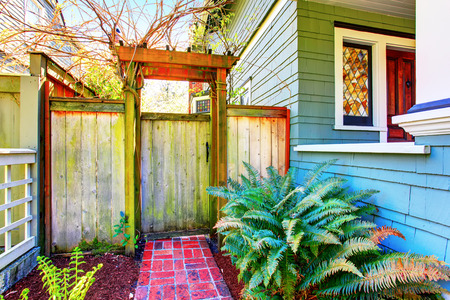 back gate: Wooden gates and fence to the backyard with side of the house. Stock Photo