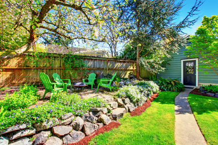 lawn area: Fenced backyard with green lawn and patio area decorated with natural stone design. Concrete walkway leading to a blue shed.
