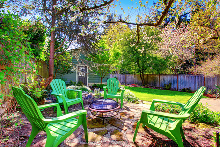 lawn area: Patio area with green chairs and natural stone floor. Fenced backyard with lawn and blue shed.